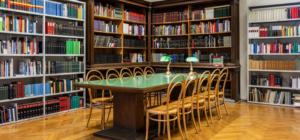 Lesesaal, Bücherwände und ein Tisch mit Sessel in der Mitte