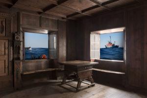 dunkle Holzbauernstube mit Fenster. dahinter liegt das Meer und Schiffe