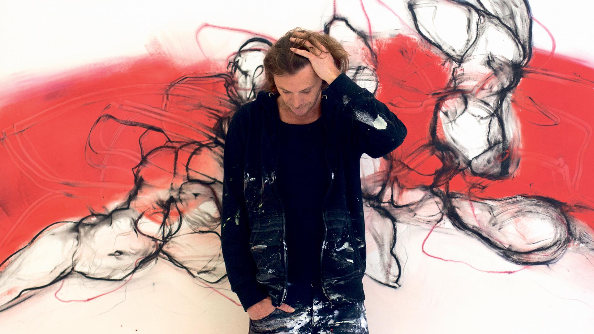 Mann neigt sich nach vorne, dahiner sein Kunstwerk - ein Bild in rot, schwarz und weiß