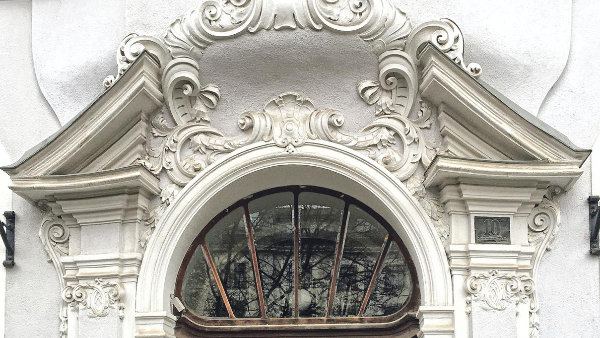 alte Eingangstür aus Eichenholz mit Glas darüber weißer Stuck