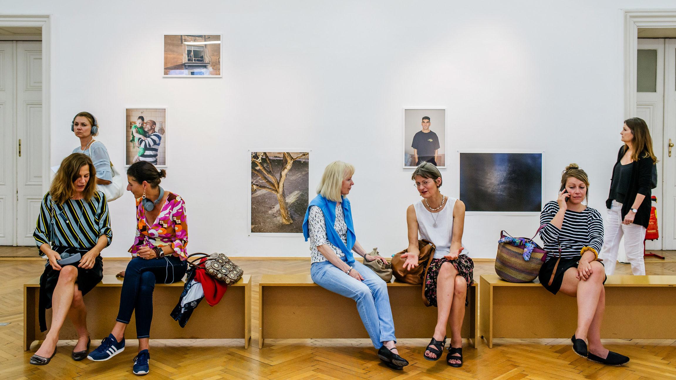 eine Gruppe Frauen sitzt auf einer Bank in einem Museum