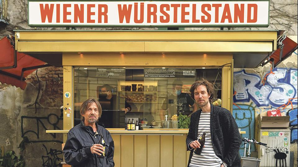 Zwei Herren mit Bierflasche in der Hand vor einem Würstelstand