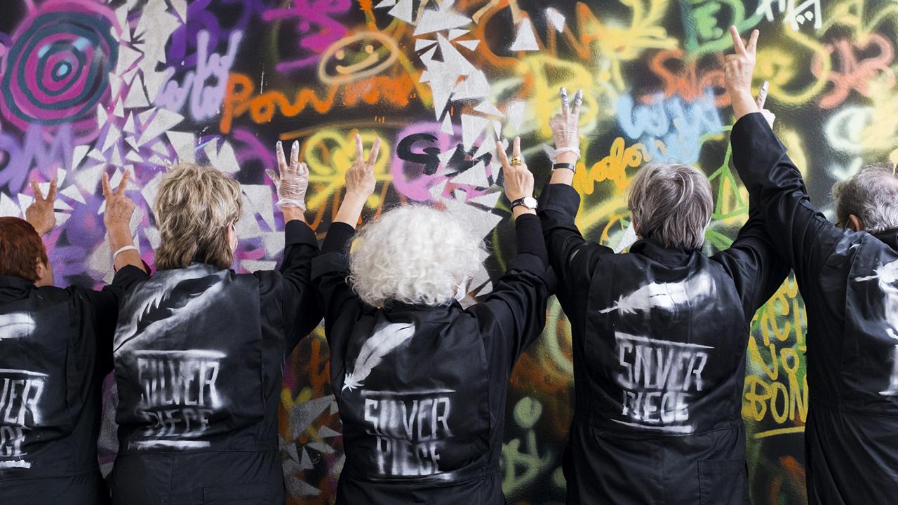 ältere Frauen bemalen eine Wand mit bunter Farbe