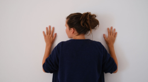 Frau berührt weisse Wand