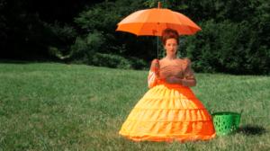 Frau mit Sonnenschirm in Wiese