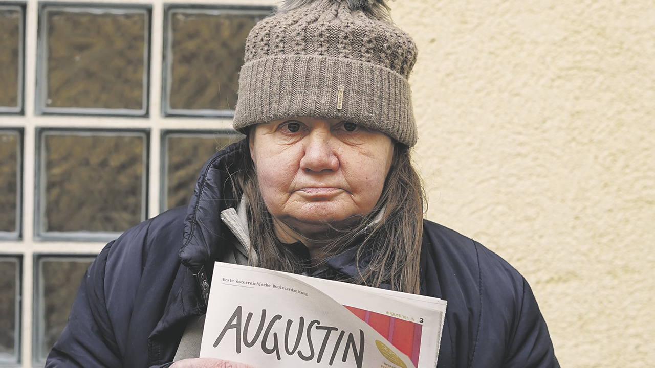 Frau mit tief ins Gesicht gezogener grauer Mütze und Straßenzeitung in der hand