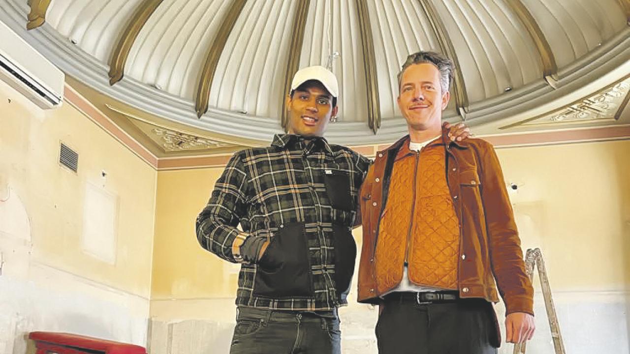 ein junger und ein älterer Mann stehen unter einer Kuppel