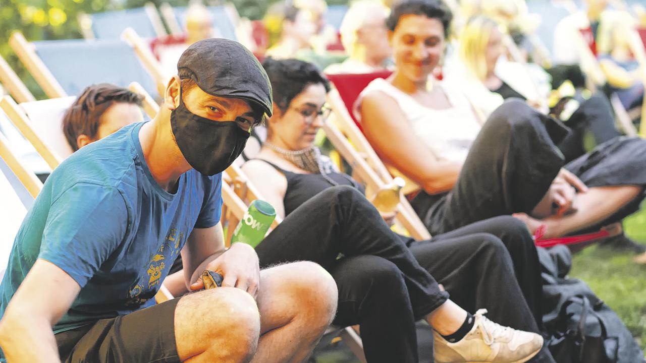 ein junger Mann mit Mundschutz und seine zwei Freunde genießen im Liegestuhl das Filmfestival