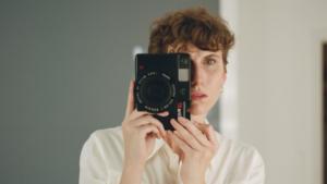 Frau blickt durch Kamera